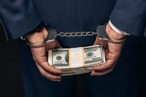 Man in formal wear in handcuffs holding money