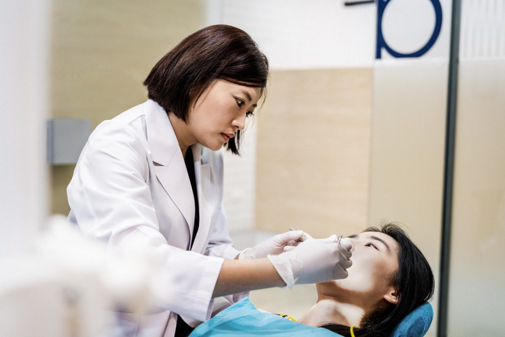Female dentist performing dentistry on patient