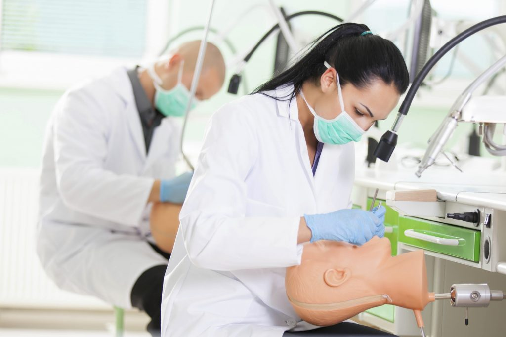 Female dental student practicing skills on dummy