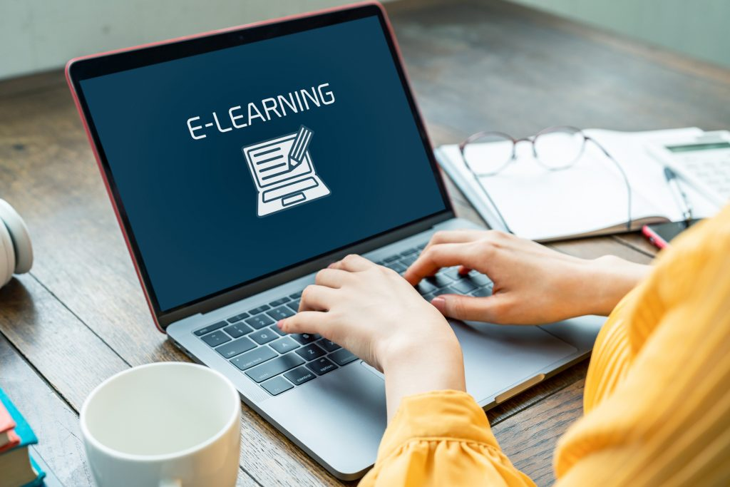 Woman typing on laptop with e-learning concept