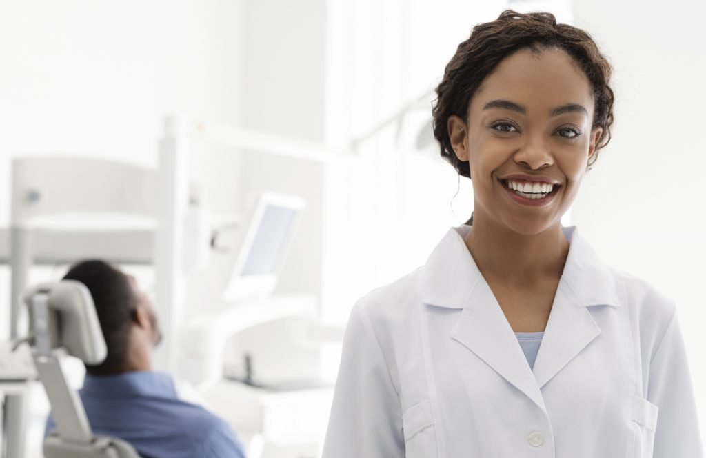 Portrait of cheerful african woman dentist over dentist cabine