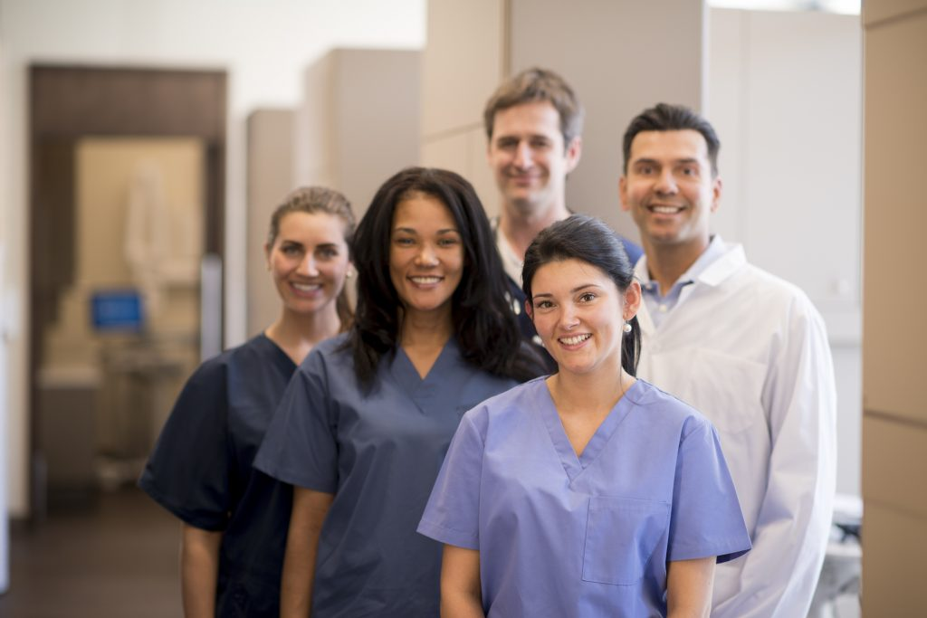 Group of smiling dental care professionals in office