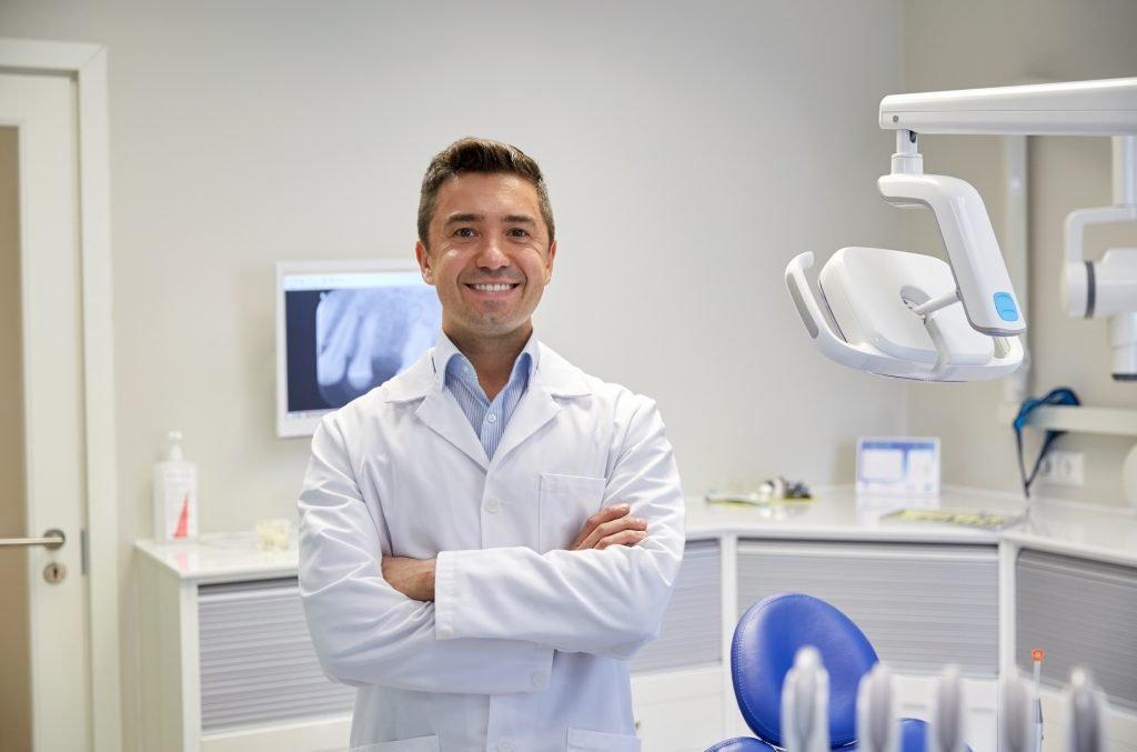 Smiling male dentist in office
