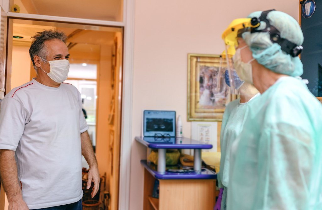 Dentist in PPE greeting patient
